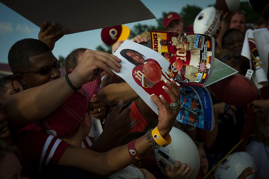 Fans line up and cram into each other, reaching and screaming out with their souvenirs to be signed by Redskins quarterback Robert Griffin III following the Redskins training camp at Redskins Park in Ashburn, Va., Monday, August 13, 2012.  (Rod Lamkey Jr./The Washington Times)