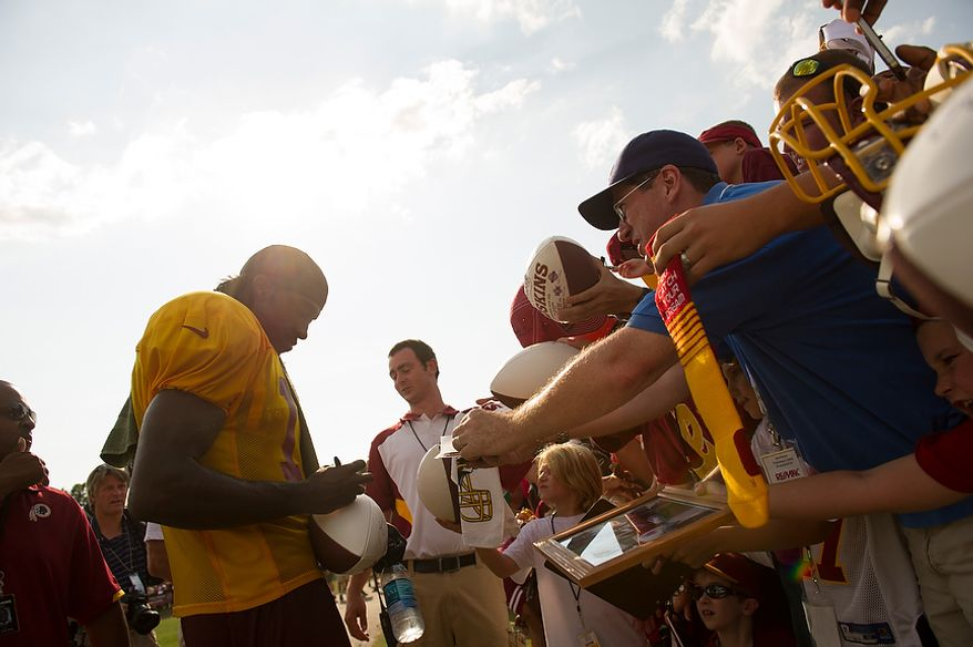 Fans line up and cram into each other, reaching and screaming out with their souvenirs to be signed by Redskins quarterback Robert Griffin III (left) following the Redskins training camp at Redskins Park in Ashburn, Va., Monday, August 13, 2012.  (Rod Lamkey Jr./The Washington Times)
