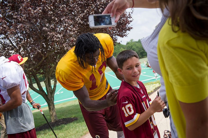 Redskins quarterback Robert Griffin III signs the jersey for an unidentified young man following Redskins training camp at Redskins Park in Ashburn, Va., Tuesday, August 14, 2012. This is the last day that fans will be able to watch their team practice in this area. Next year the Redskins will move their practice facility to the Richmond, Va., area. (Rod Lamkey Jr./The Washington Times)