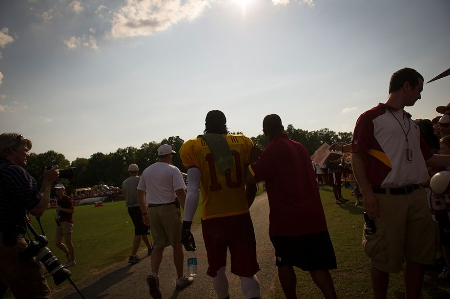 Redskins quarterback Robert Griffin III makes his way to the locker room following the Redskins training camp at Redskins Park in Ashburn, Va., Monday, August 13, 2012.  (Rod Lamkey Jr./The Washington Times)