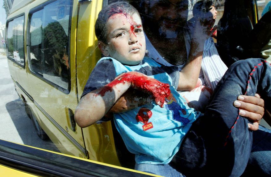 A Syrian boy arrives at a field hospital after an airstrike hit homes on the outskirts of Aleppo on Wednesday. As bloodshed increases in Syria, critics say President Obama has relied too heavily on the United Nations. (Associated Press)