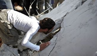 A Syrian man looks for survivors Aug. 15, 2012, under the rubble of destroyed houses after an air strike in the town of Azaz, Syria, on the outskirts of Aleppo. (Associated Press)