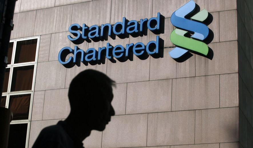 A man walks past the Standard Chartered Bank building in Hong Kong in October 2010. (AP Photo/Kin Cheung)