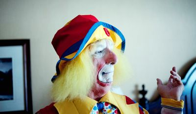 """Bob Neil, aka """"Kiwi"""" the clown, gestures after making the finishing touches on his costume at the third annual Clown Campin' in Ontario, Calif.  (AP Photo/Grant Hindsley)"""