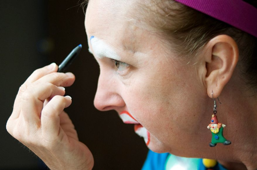 """Laura Sicklesteel, or """"Molly the Clown"""" puts on makeup while getting into character at the third annual Clown Campin' in Ontario, Calif. The week long event is held for clowns across the United States and Canada to learn, get inspired, and network. (AP Photo/Grant Hindsley)"""