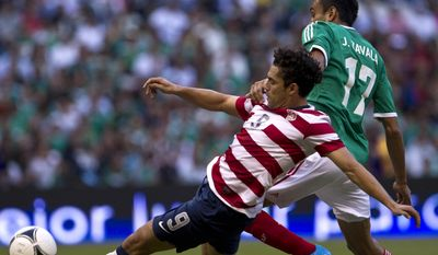 Mexico's Jesus Zabala, back, fights for the ball with U.S. Herculez Gomez during a friendly soccer match in Mexico City, Wednesday, Aug. 15, 2012. (AP Photo/Christian Palma)