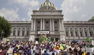 Hundreds of demonstrators descend on the Capitol in Harrisburg, Pa., on Tuesday, July 24, 2012, to protest a tough new voter ID law. (AP Photo/The Harrisburg Patriot-News, John C. Whitehead)