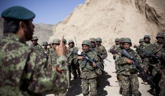 **FILE** Afghan National Army Lt. Col. Abdul Wakil Warzajy (left), battalion commander, gives orders to soldiers of the First Battalion before they set out on a search and capture mission towards the village of Noor Khiel village, Logar province, eastern Afghanistan. (Associated Press)