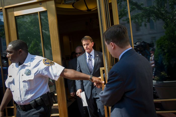 Escorted by a security guard, Family Research Council President Tony Perkins arrives to offer remarks and field questions from reporters outside of the Family Research Council headquarters in Washington, D.C., Thursday, August 16, 2012. (Rod Lamkey Jr./The Washington Times)