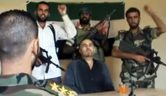 This image made from amateur video released by the Shaam News Network purports to show Syrian Pilot Col. Rafik Mohammed Suleiman being interrogated by a rebel officer Aug. 13, 2012, after his Soviet-made MiG warplane was apparently hit by ground fire over Deir el-Zour province, an area near the Iraqi border. (Associated Press/Shaam News Network)