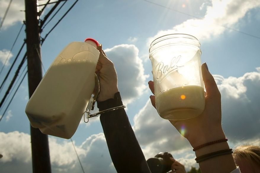 Demonstrators raise glasses and jugs of raw milk in a toast Nov. 1, 2011, during a protest in front of the Food and Drug Administration headquarters in Silver Spring, Md. The FDA has banned interstate transportation of raw milk. The milk used during the demonstration was picked up in Pennsylvania and transported to Maryland. (Rod Lamkey Jr./The Washington Times)