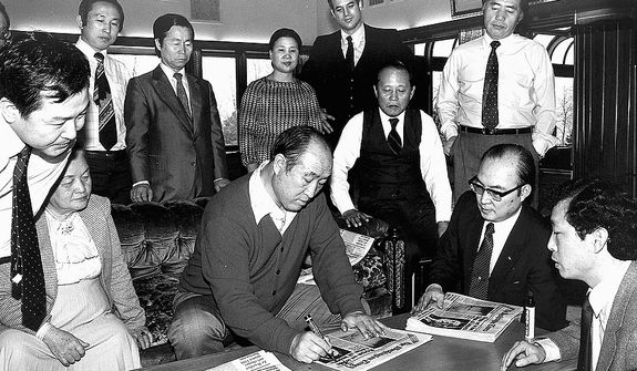 The Rev. Sun Myung Moon autographs an early edition of The Washington Times with supporters.  Courtesy H.S.A.-U.W.C.