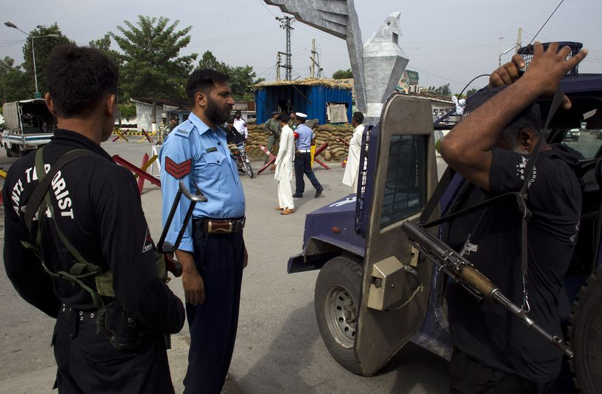 Pakistani police commandos wait to enter an air force base in Kamra, about 85 kilometers (50 miles) northwest of Islamabad, Pakistan, on Aug. 16, 2012, after at least half a dozen militants attacked the base before dawn, sparking a heavy battle that killed two security personnel and left parts of the base in flames, officials said. (Associated Press)