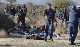 Police surround the bodies of striking miners after opening fire on a crowd at the Lonmin Platinum Mine near Rustenburg, South Africa, on Aug. 16, 2012. (Associated Press)