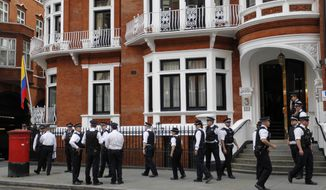 British police officers stand guard outside the Ecuadorian Embassy in central London on Aug. 16, 2012, after Ecuadorean Foreign Minister Ricardo Patino announced that he had granted political asylum to WikiLeaks founder Julian Assange. (Associated Press)