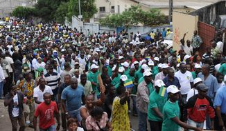 In this photo taken Wednesday, Aug. 15, 2012, people walk through the Ancien Sobraga neighborhood as they head to the meeting point for an opposition protest march, in Libreville, Gabon. A leader of an opposition party in Gabon said Wednesday that three women were killed and about 30 people wounded, following a banned demonstration that turned violent. (AP Photo/Joel Bouopda Tatou)