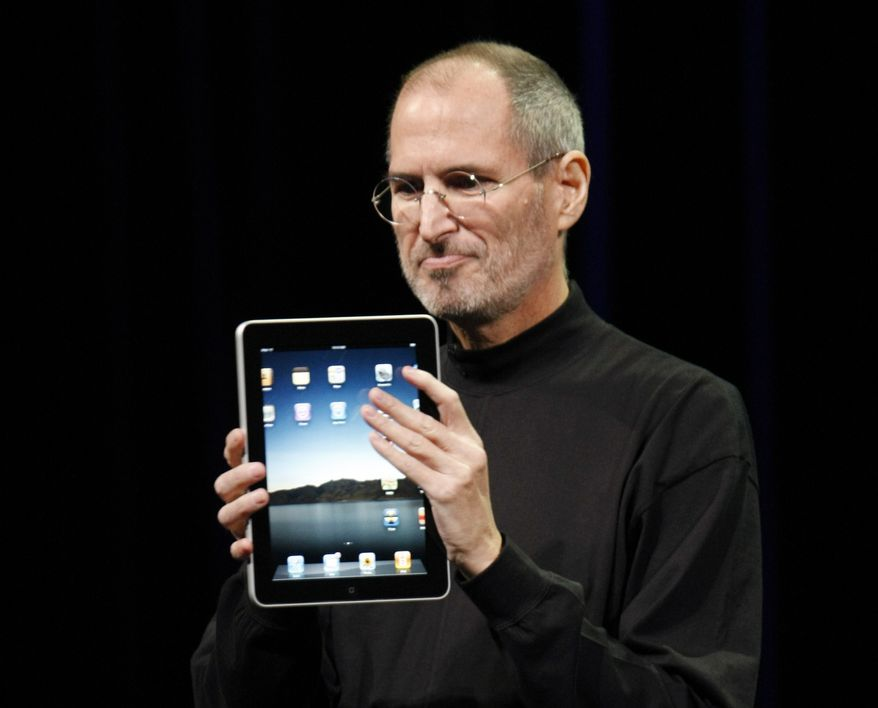 ** FILE ** In this Jan. 27, 2010, file photo, Apple CEO Steve Jobs shows off the new iPad during an event in San Francisco. (AP Photo/Paul Sakuma, File)