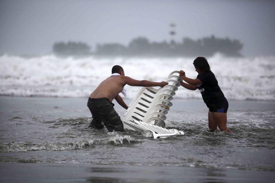 ** FILE ** Vendors that were caught unprepared try to recover their chairs after high waves dragged their beach stalls into the sea in Veracruz, Mexico, Thursday, Aug. 9, 2012. Tropical Storm Ernesto headed into Mexico's southern Gulf coast as authorities in the flood-prone region prepared shelters, army troops and rescue personnel for drenching rains. (AP Photo/Felix Marquez)