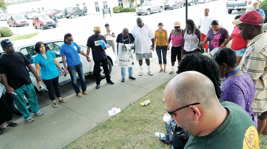 ** FILE ** People form a circle Tuesday, Aug. 14, 2012, in front of Jonesboro, Ark., City Hall during a march to protest the shooting death of Chavis Carter, 21, of Southaven, Miss. Carter died July 28 while sitting handcuffed in the back of a patrol car. The protest was coordinated by the Commission on Religion and Racism. (AP Photo/The Jonesboro Sun, Keith Inman)