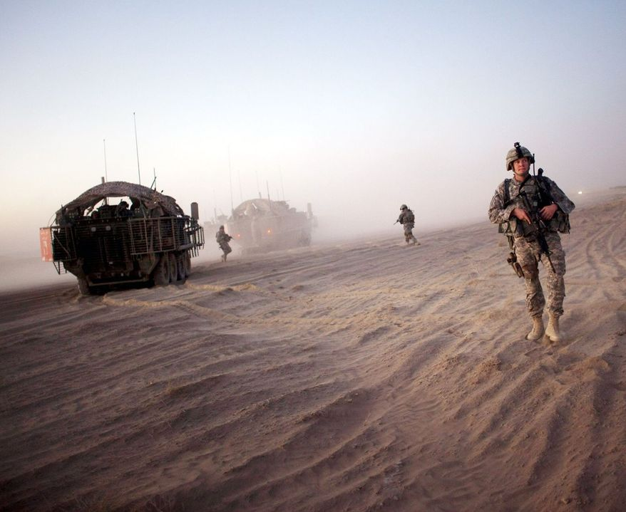 U.S. soldiers from the 5th Stryker Brigade take positions near their armored vehicles during a patrol on the outskirts of Spin Boldak, Afghanistan, in August 2009. Months later, they got the anti-IED gear they requested.  (Associated Press)