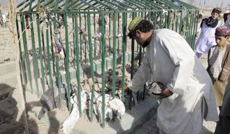 An Afghan man collects victims' belongings at the scene of an explosion at a cemetery in Lashkar Gah, southwest of Kabul, Afghanistan, on Sunday, Aug. 19, 2012. (AP Photo/Abdul Khaleq)