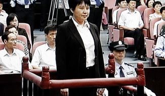 **FILE** Gu Kailai (center), the wife of disgraced politician Bo Xilai, stands during her trial Aug. 9, 2012, in the Hefei Intermediate People's Court in Hefei in eastern China's Anhui province. The fallen Chinese politician's wife confessed to killing a British businessman. (Associated Press/CCTV via APTN)