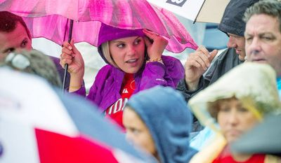 Nationals fan Hannah Sission, of Richmond, Va., joins her brother Josh Sission, of Washington, D.C., under an umbrella during a rain delay for the start of the game as the Washington Nationals host the New York Mets at Nationals Park in Washington, D.C., Sunday, August 19, 2012. (Rod Lamkey Jr./The Washington Times)