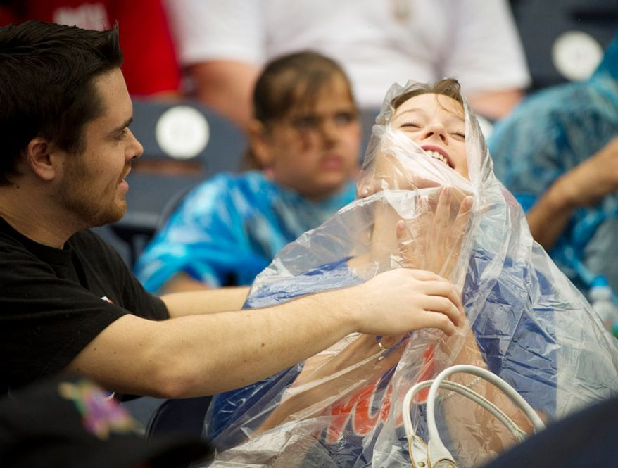 Mets fan Nicholas Harris (left) helps his girlfriend Caitlin O' Malley with her rain poncho during a rain delay. (Rod Lamkey Jr./The Washington Times)