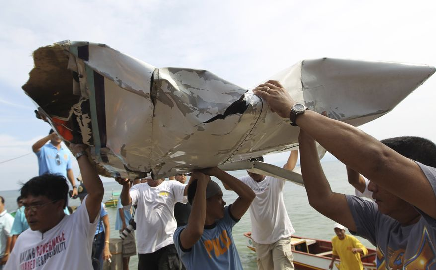 Men carry parts of a crashed plane that was carrying Philippine Interior Secretary Jesse Robredo in Masbate, Philippines, on Sunday, Aug. 19, 2012. About 300 rescuers were searching for Mr. Robredo and his two pilots after their small plane crashed into the sea while attempting an emergency landing Saturday. (AP Photo/Malacanang Photo Bureau, Jay Morales)
