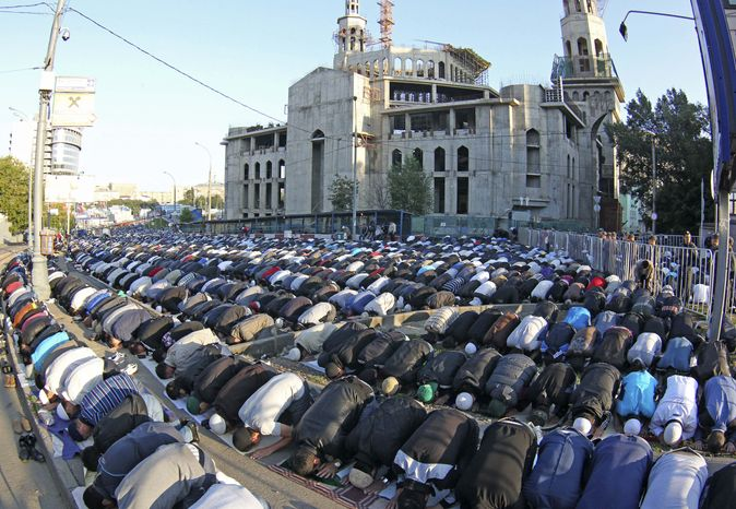 Thousands of Russian Muslims perform Eid al-Fitr prayers outside the main mosque in Moscow on Sunday, Aug. 19, 2012, to mark the end of the holy fasting month of Ramadan. (AP Photo/Mikhail Metzel)