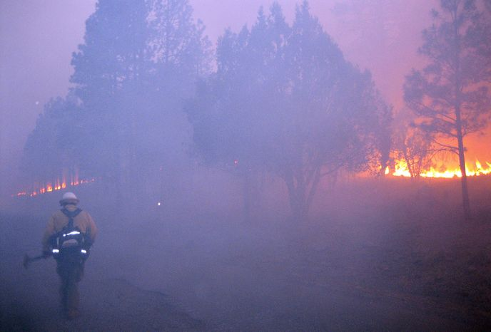 **FILE** A firefighter walks along a burnout line along a large wildfire in the Gila National Forest in New Mexico on May 29, 2012. (Associated Press/U.S. Forest Service)