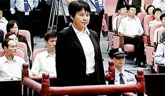 Gu Kailai (center), the wife of disgraced politician Bo Xilai, stands during her trial in the Hefei Intermediate People's Court in Hefei in eastern China's Anhui province earlier this month. Gu was given a suspended death sentence on Monday. (Associated Press)