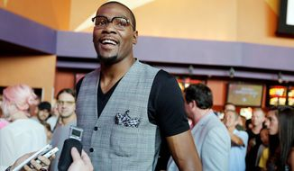 "Basketball star Kevin Durant walks the red carpet Sunday during the premiere of his new movie, ""Thunderstruck,"" in Oklahoma City. The three-time NBA scoring champion and Olympic gold medalist plays himself in the film, about a fan who magically absorbs Durant's skill set. (The Oklahoman via Associated Press)"