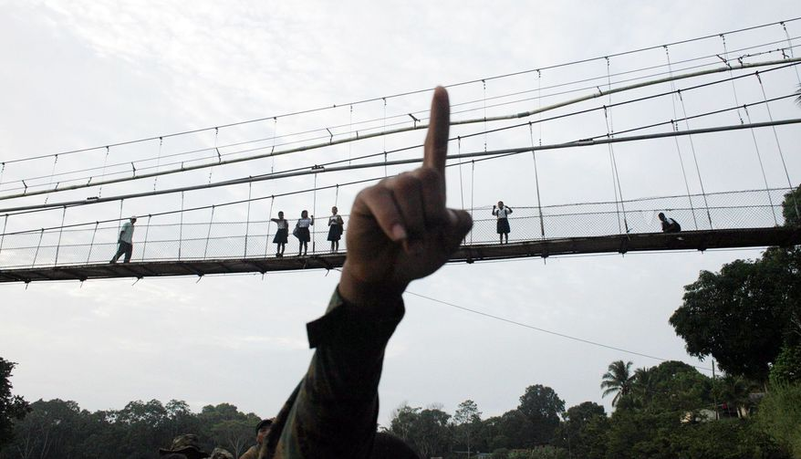 A Panamanian border police officer points as he begins his patrol in Darien province, on the border with Colombia, in Yaviza, Panama. Panamanian authorities began noticing five years ago that the Darien Gap, the only interruption in the Pan-American Highway, was being used by migrant smugglers. (Associated Press)