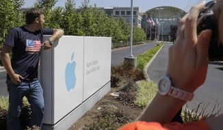 Russian tourists pose Aug. 20, 2012, outside of Apple headquarters in Cupertino, Calif. (Associated Press)