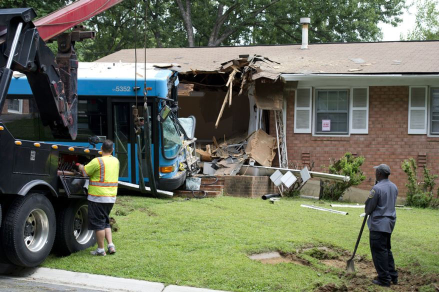 """A tow truck operator slowly removes a Ride On bus that crashed into a home in the 9400 block of Avenel Road in Silver Spring, Md. on Monday, Aug. 20, 2012. No one in the home was hurt. Nine people from the bus, including the bus driver, are being evaluated for injuries. Homeowner Femi Olamide, who was arriving home at the time, says he saw that the bus was not going to stop at the stop sign and got back into his car. The bus sped past him and crashed into his home. """"I grabbed my Bible [which was on the seat of my car,] and said, 'Thank you, God,' """" he says. (Barbara L. Salisbury/The Washington Times)"""
