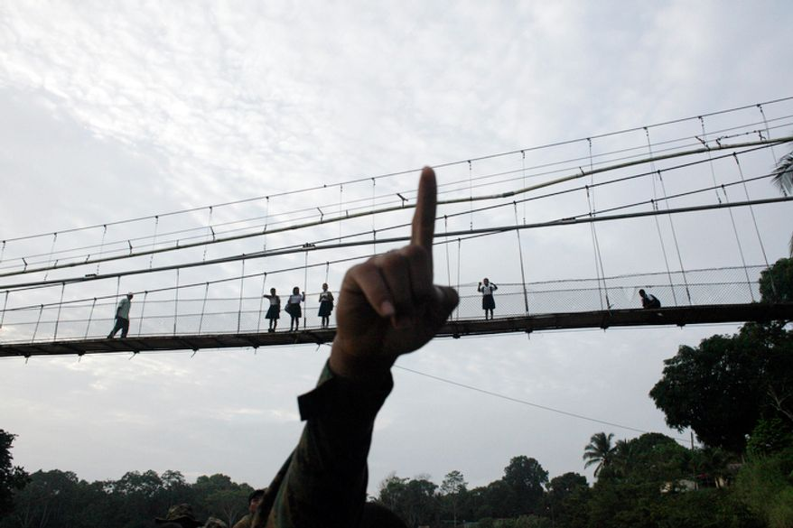 A Panama border police officer points as he begins to patrol in the Darien province, on the border with Colombia, in Yaviza, Panama. Panamanian authorities began noticing five years ago that the Darien Gap, the only interruption in the Pan-American Highway, was being used by migrant smugglers, usually to move people from Asia and Africa.  (AP Photo/Arnulfo Franco)