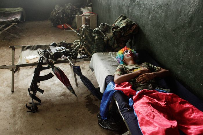 A Panama border police officer dressed as a clown rests on a cot before entertaining residents of the Darien province, on the border with Colombia, in Union Choco, Panama.  (AP Photo/Arnulfo Franco)