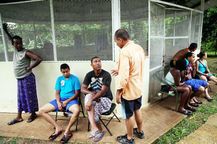 Cuban migrants gather as they rest at a shelter along with another group of migrants from Bangladesh, after being found by Panamanian border police in the Darien province in Meteti, Panama. (AP Photo/Arnulfo Franco)