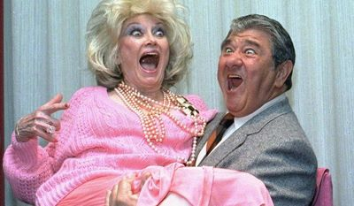 In this Oct. 9, 1985, file photo, Comedian Phyllis Diller gets a lift from emcee Buddy Hackett prior to the celebrity stag luncheon roast at the New York Friars Club in New York City. (AP Photo/Marty Lederhandler, File)