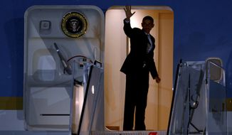 President Obama waves Aug. 6, 2012, as he boards Air Force One at John F. Kennedy International Airport in New York after attending two fundraisers in Connecticut. (Associated Press)