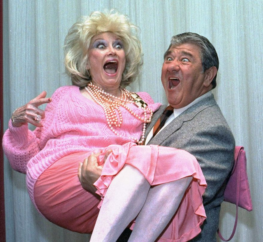 **FILE** Comedian Phyllis Diller gets a lift from emcee Buddy Hackett prior to the celebrity stag luncheon roast at the New York Friars Club in New York City on Oct. 9, 1985. (Associated Press)