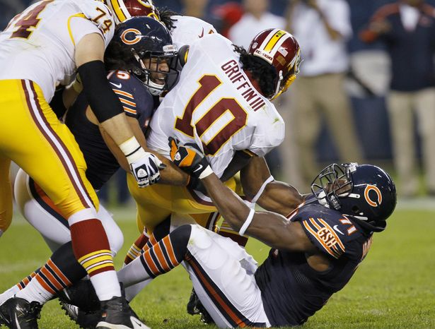 Washington Redskins quarterback Robert Griffin III (10) is tackled by Chicago Bears defensive end Israel Idonije (71) and defensive tackle Matt Toeaina (75) during the first half of an NFL preseason football game in Chicago on Saturday, Aug. 18, 2012. At left is Redskins offensive tackle Tyler Polumbus. (AP Photo/Charles Rex Arbogast)
