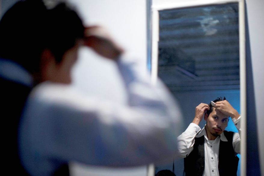 A dancer combs his hair before a mirror before competing during the 2012 Tango Dance World Cup in Buenos Aires, Argentina, Monday, Aug. 20, 2012.  (AP Photo/Natacha Pisarenko)