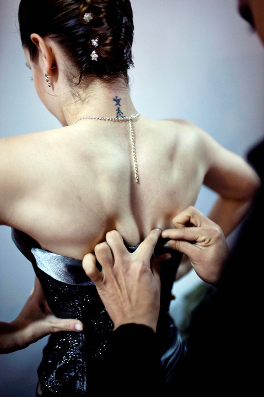 A dancer is helped to dress backstage before competing during the 2012 Tango Dance World Cup.  (AP Photo/Natacha Pisarenko)