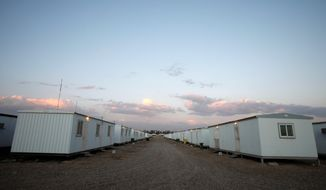 In this photograph made on Friday, Feb. 17, 2012, rows of housing containers formerly occupied by the US military are seen at Baghdad, airport. Iraqi government plans to move here some 3,300 members of the People's Mujahedeen Organization of Iran, who spent past three decades at Camp Ashraf, northeast of Baghdad. (AP Photo/Karim Kadim)
