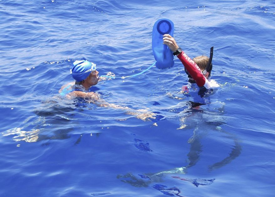 American endurance swimmer Diana Nyad is hydrated by a crew member in the Florida Straits between Cuba and the Florida Keys on Monday, Aug. 20, 2012. (AP Photo/Diana Nyad via the Florida Keys News Bureau, Christi Barli)