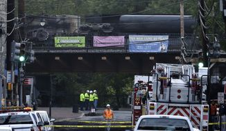 Officials stand underneath a bridge where part of a CSX freight train derailed on Tuesday, Aug. 21, 2012, in Ellicott City, Md. (AP Photo/Patrick Semansky)