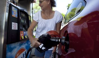 Suzanne Meredith of Walpole, Mass., gases up her car at a Gulf station in Brookline, Mass., on Tuesday, July 10, 2012. (AP Photo/Steven Senne)