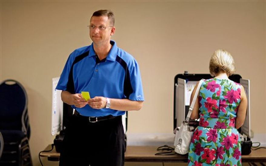 State Rep. Doug Collins, left, leaves a voting booth after casting his ballot along with his wife Lisa, right, Tuesday, Aug. 21, 2012, in Gainesville, Ga. Republican voters in north Georgia chose Rep. Collins, a lawmaker with ties to the governor, over conservative talk show host Martha Zoller. (AP Photo/David Goldman)